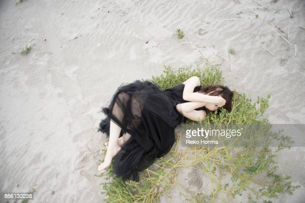 Woman lying on the grass covering her eyes