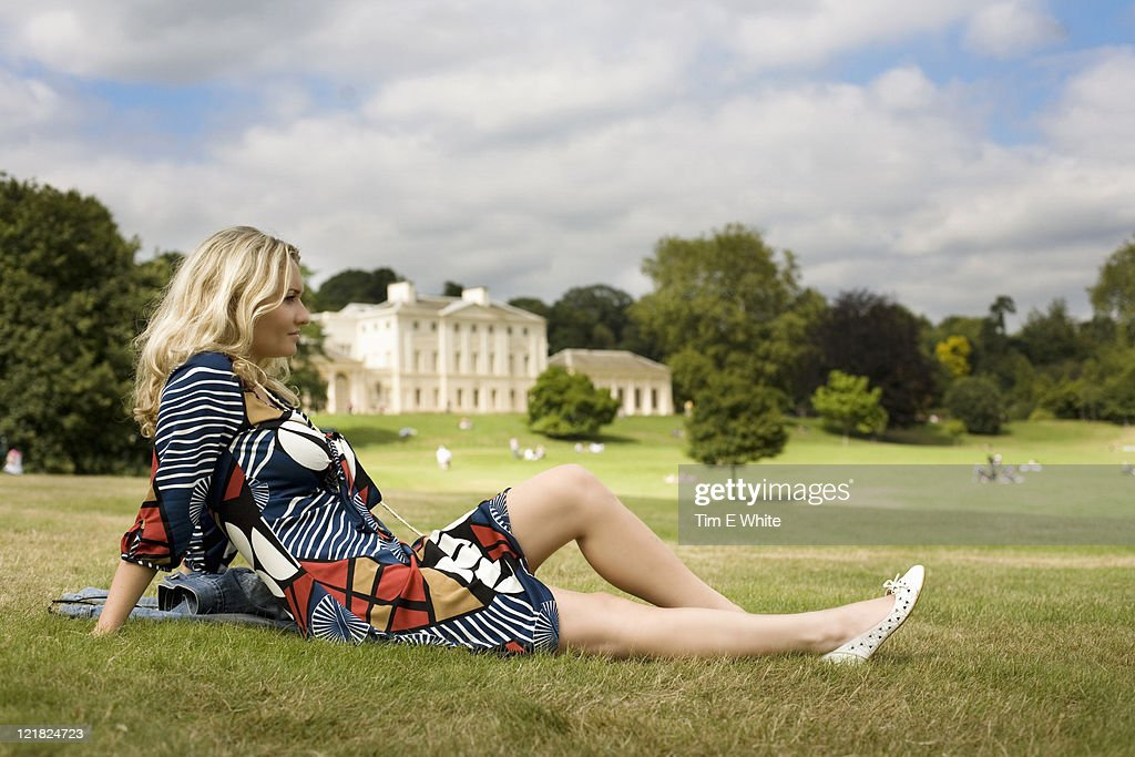 Woman lying on the grass in front of Kenwood House, Hampstead Heath, London, UK : Stock Photo