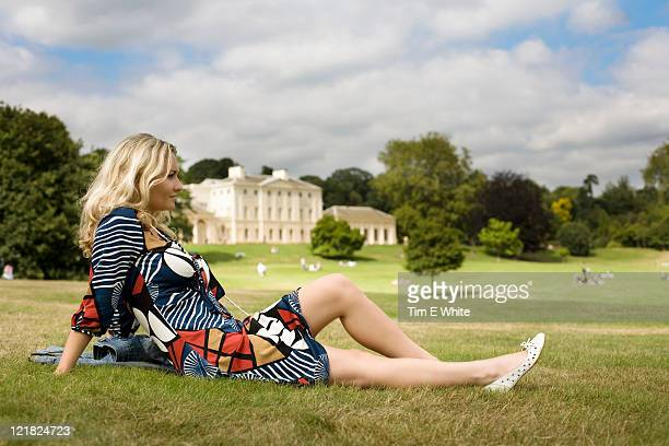 woman lying on the grass in front of kenwood house, hampstead heath, london, uk - kenwood house stock pictures, royalty-free photos & images
