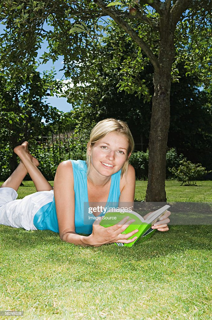 Woman lying on the grass reading a book : Stock Photo