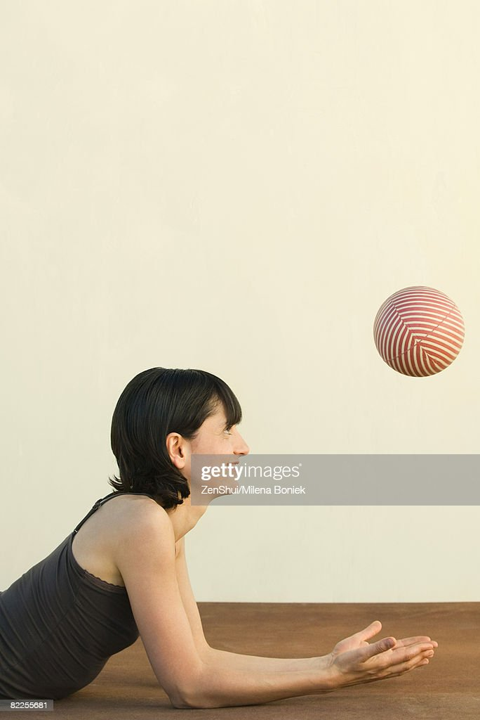 Woman lying on the ground, catching ball, side view : Stock Photo