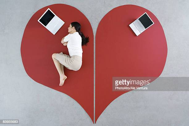 Woman lying on the ground with laptop on large broken heart, abandoned laptop behind her