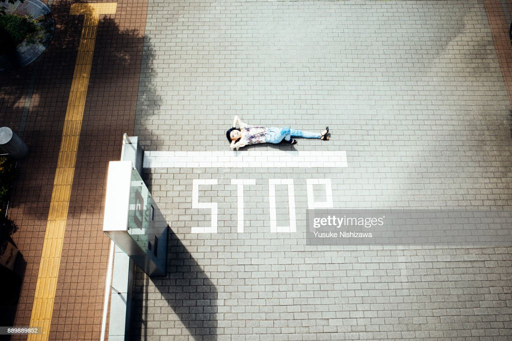 A woman lying on the road : Stock Photo