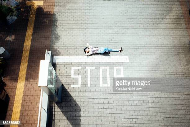 a woman lying on the road - offbeat stock photos and pictures