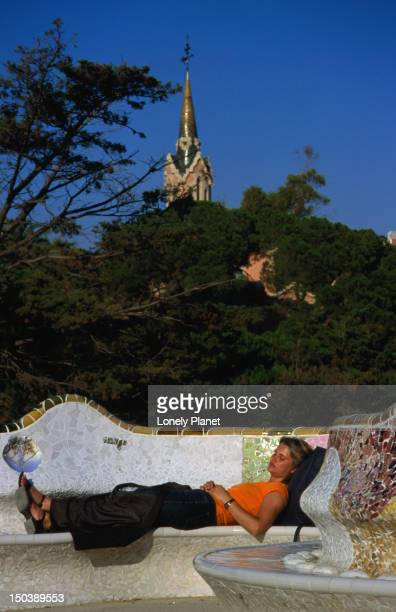 Woman lying on tiled benches of Gaudi's Parc Guell.