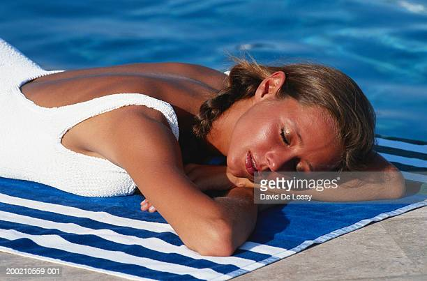 Woman lying on towel by pool