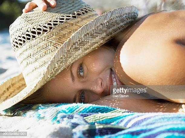 Woman lying on towel, hat shielding face, portrait, ground view