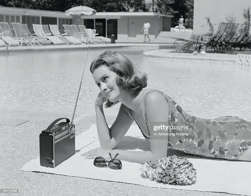 Woman lying on towel poolside listening to radio with antenna up. : Stock Photo
