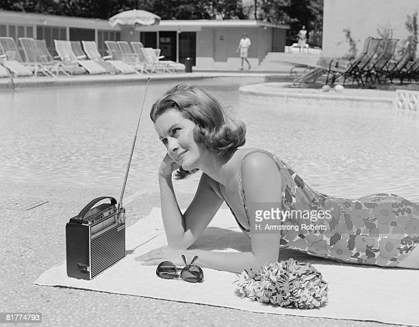 woman lying on towel poolside listening to radio with antenna up. - sixties photos et images de collection