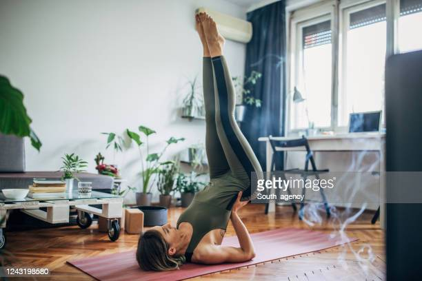 woman lying on upper back and holding her lower back in balance - estilo de vida ativo imagens e fotografias de stock