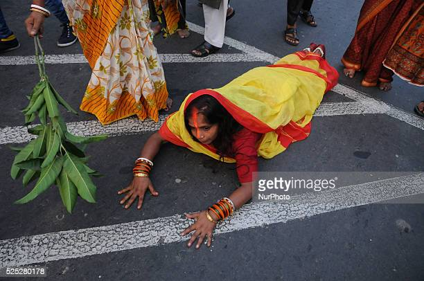 A woman lying prostrate worshiping the Sun god during Chhat puja on a road in Kolkata before going to the Hooghly river Chhath is an ancient Hindu...