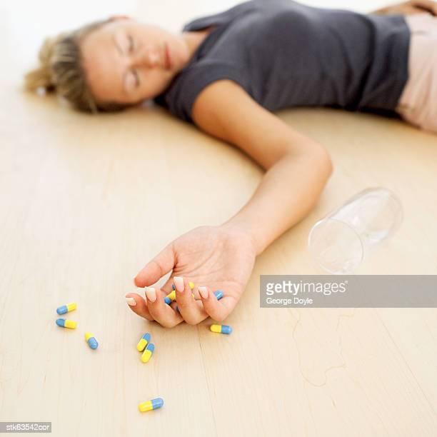 woman lying unconscious on the floor with capsules in her hand - suicidio pastillas fotografías e imágenes de stock