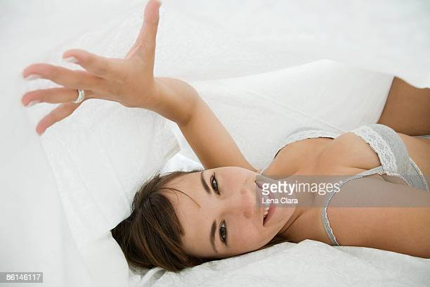 A woman lying under bed covers