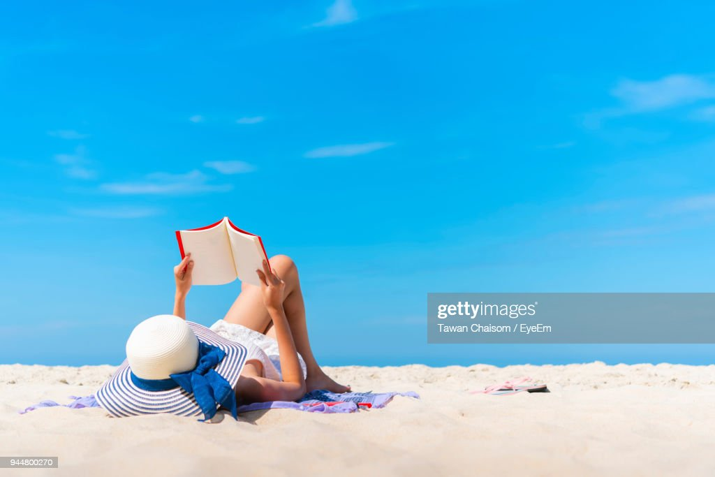 Woman Lying While Reading Book On Beach Against Blue Sky : Stock Photo