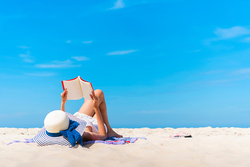 Woman Lying While Reading Book On Beach Against Blue Sky - gettyimageskorea