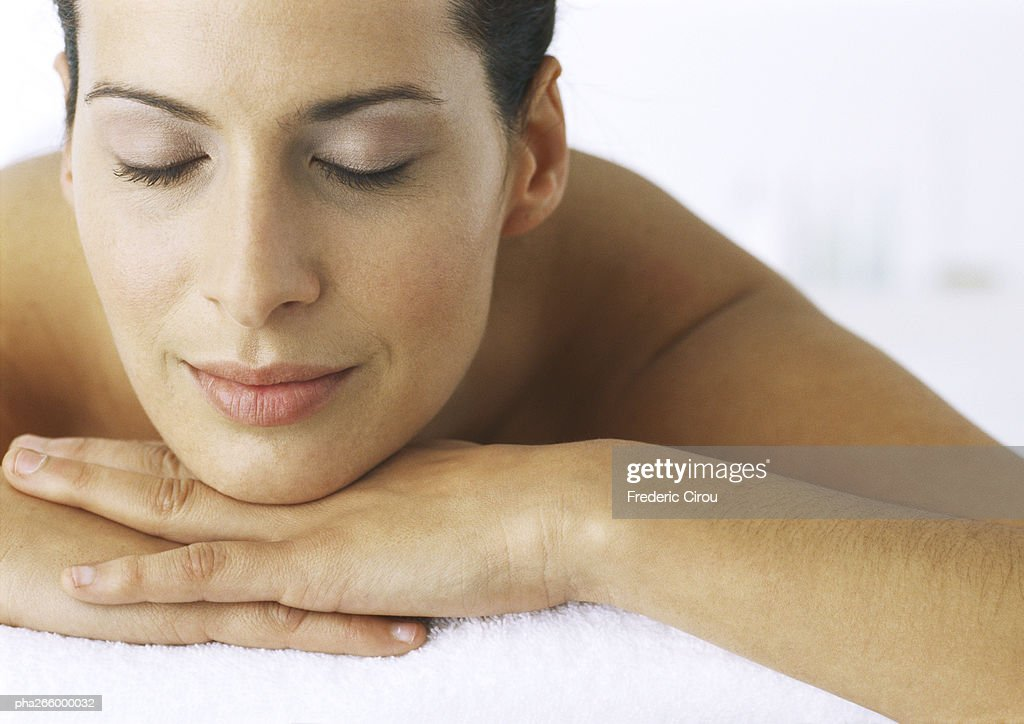 Woman lying with chin resting on hands, eyes closed, close-up : Stockfoto