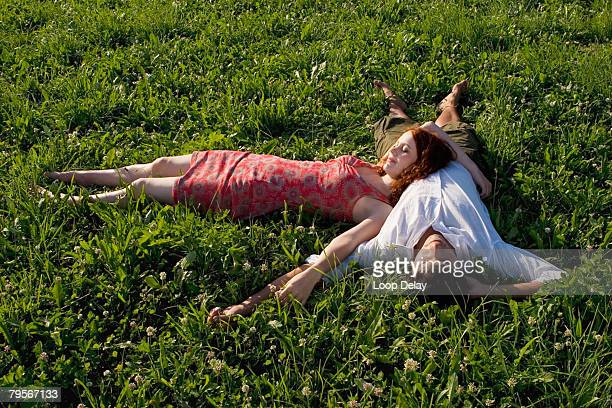 Woman lying with head on man's belly in meadow