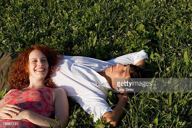 Woman lying with head on man's belly, smiling