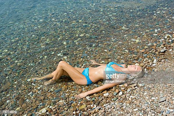 Woman lying with legs in the sea