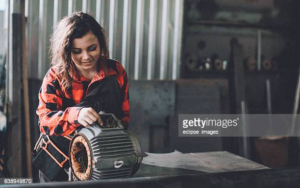 Woman machinist examining electric motor with voltmeter