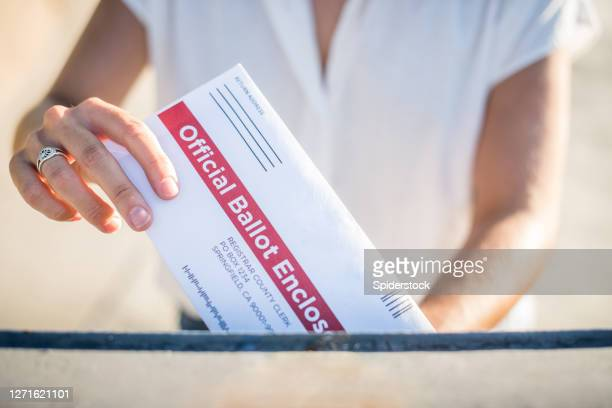 woman mailing her absentee voter ballot - voter registration stock pictures, royalty-free photos & images