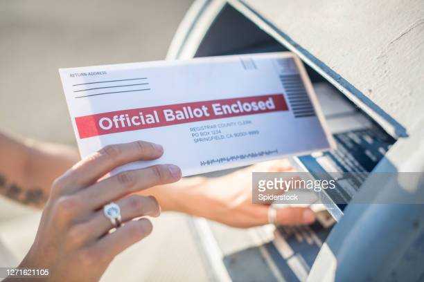 woman mailing her absentee voter ballot - voting by mail stock pictures, royalty-free photos & images