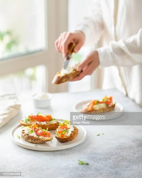 la donna fa bruschetta con salmone, cagliata e cetriolo su pane tostato in stile high key su sfondo bianco. - salmone affumicato foto e immagini stock