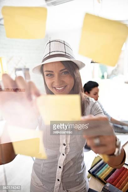 Woman make scheme on sticky notes on glass board