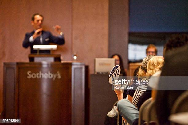 A woman makes a bid as Tobias Meyer an auctioneer at Sotheby's auctions off Lehman Brother's art collection in New York on Saturday September 25 2010...