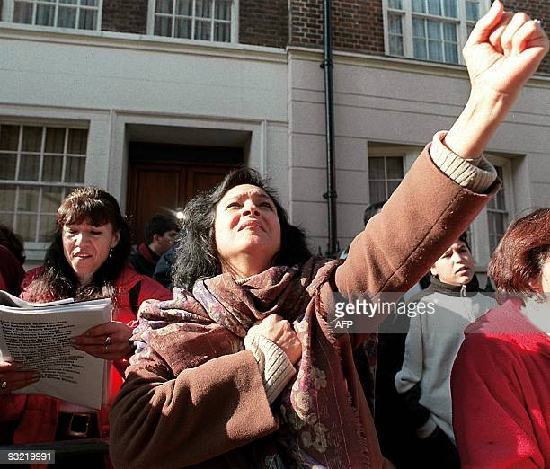 A woman makes a gesture of defiance as demonstrators shout slogans and hold placards 1 8 October at the entrance to The London Clinic where former...