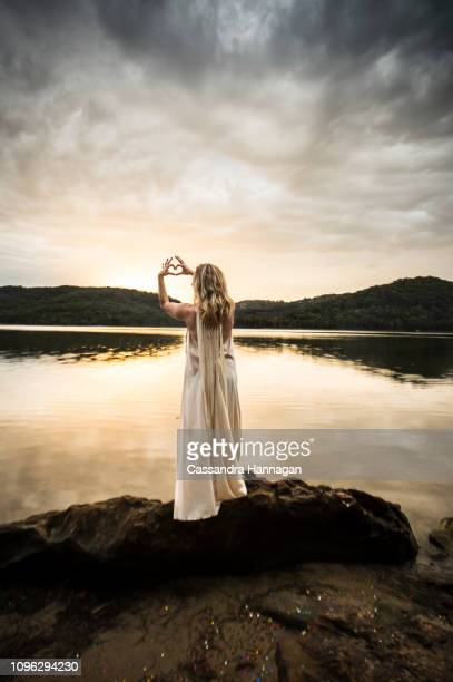 a woman makes a heart shape with her hands by a lake - mystic goddess stock photos and pictures