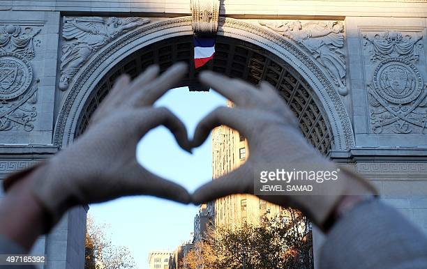 A woman makes a heart sign with her fingers as a French national flag is placed on the arch at the Washington Square Park during a vigil to show...