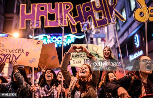 TOPSHOT A woman makes a heart sign with her hands as people hold signs reading 'no' as they march down Istiklal Avenue during a feminist night march...