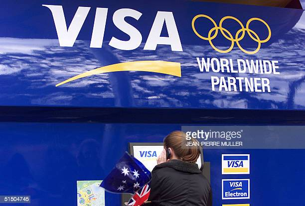 A woman makes a phone call as she gets money in a Visa automatic teller machine 15 September 2000 in the Olympic Park before the opening ceremony of...