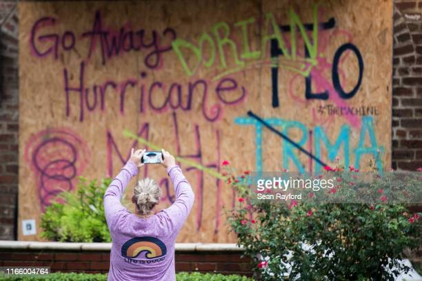 A woman makes a photo of a boarded up hotel on September 4 2019 in Charleston South Carolina Forecasts expect Hurricane Dorian's arrival to the...