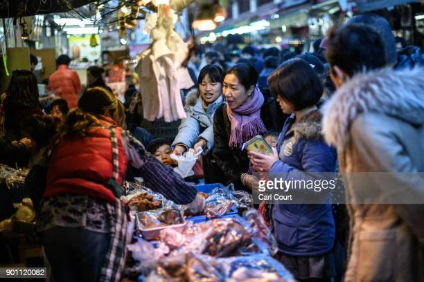 A woman makes a purchase from a stall in Ameya Yokocho market on January 4 2018 in Tokyo Japan Ameya Yokocho claimed to be Tokyo's last remaining...