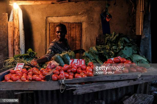 Woman makes a selection of the most expensive tomatoes for a customer just before the 7PM curfew in Kibera, Nairobi on May 05, 2020. - The Kibera...