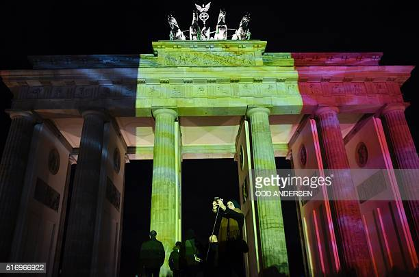 A woman makes a selfie photo as the colors of the Belgian flag are projected on to the Brandenburg Gate in Berlin as the German capital shows its...