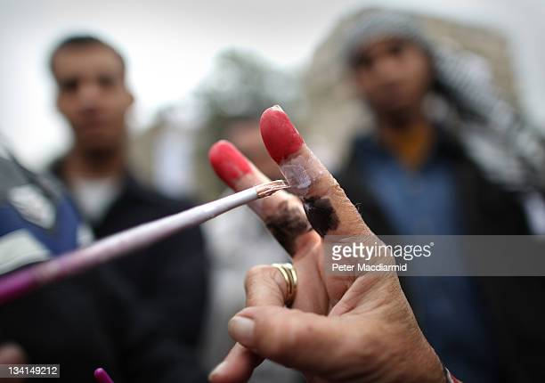 A woman makes a victory sign as her fingers are painted with the colours of the Egyptian flag in Tahrir Square on November 27 2011 in Cairo Egypt...