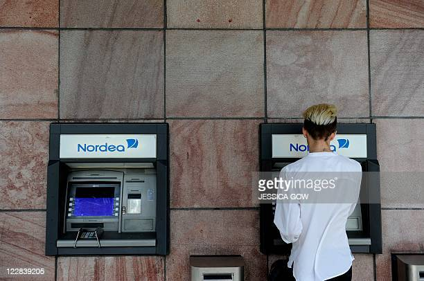 A woman makes a withdrawal from Nordea automatic teller machine in central Stockholm on August 29 2011 Nordea the biggest Nordic bank which today...