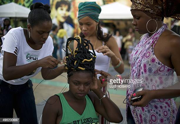 A woman makes an AfroColombian hairstyle during the 10th contest of Afrohairdressers Tejiendo Esperanzas on June 1 in Cali Valle del Cauca department...