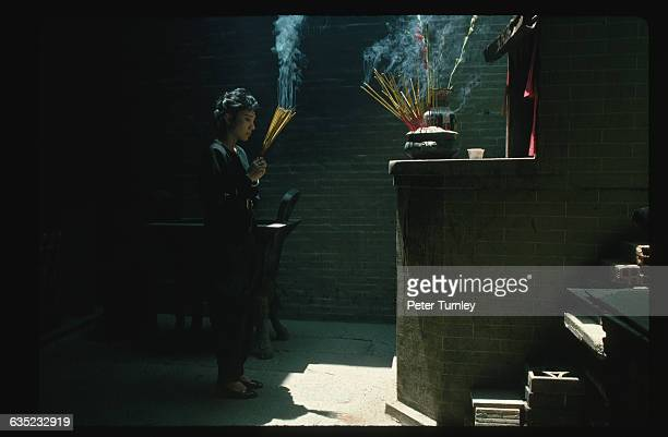 A woman makes an offering of joss sticks at the Thien Hau Pagoda a temple built in the early 1800s to honor the Goddess of the Sea