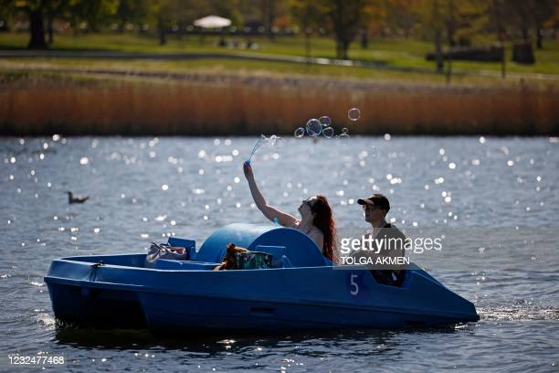 Woman makes bubbles while using a pedal boat on the Serpentine in Hyde Park in the Spring sunshine in London on April 23, 2021. - Under the relaxing...