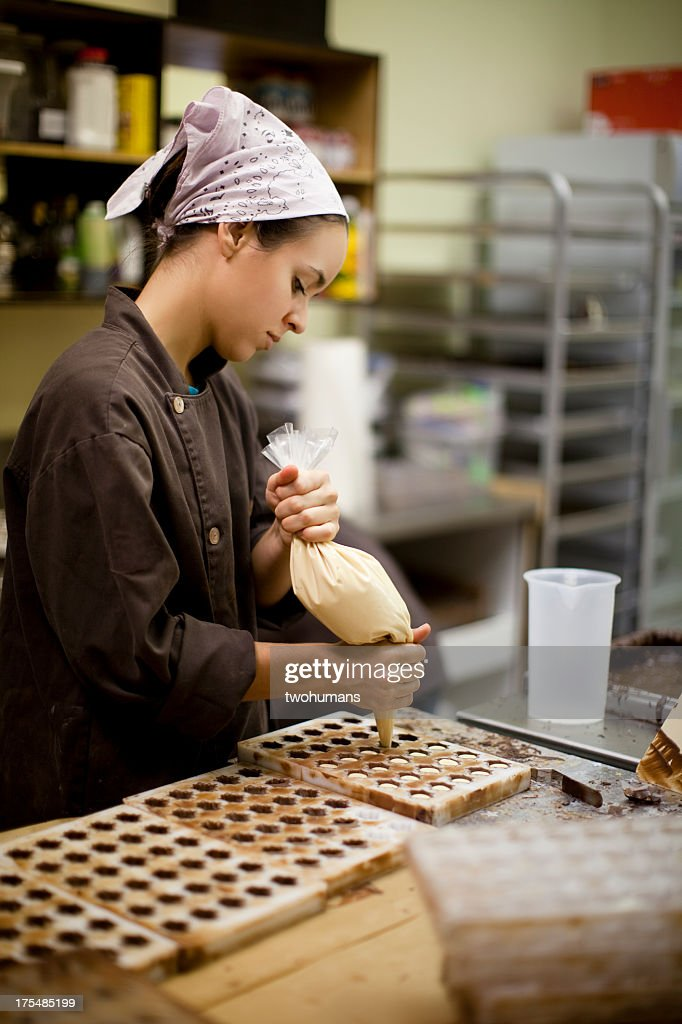A woman makes chocolate bonbons in an industrial kitchen : Stock Photo