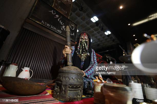 "Woman makes coffee at ""Palestine Cultural Heritage"" exhibition organized for cultural representation to mark the 43rd anniversary of Palestinian Land..."