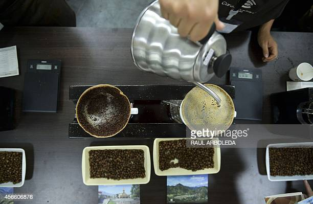 A woman makes coffee during the Colombian coffee Expoespeciales Cafe de Colombia fair in Medellin Antioquia department Colombia on October 3 2014 The...
