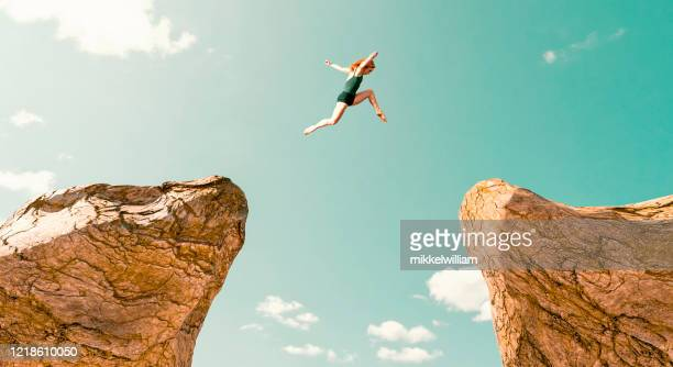 woman makes dangerous jump between two rock formations - cambiamento foto e immagini stock
