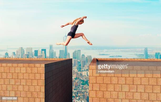 woman makes dangerous jump over gap between two tall buildings - high up stock pictures, royalty-free photos & images