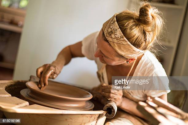 Woman makes hand made ceramics from clay VIII