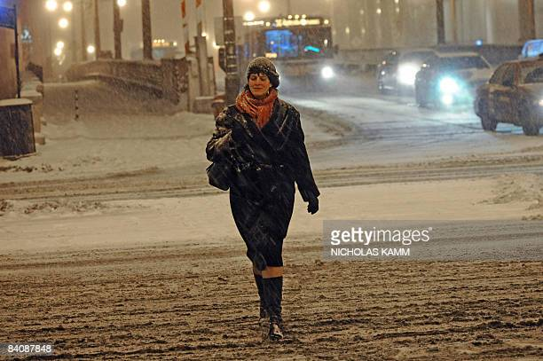 A woman makes her way across a street during a snow storm in Chicago early December 19 2008 Up to 30cm of snow was expected to fall overnight AFP...